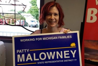 Patty Malowney holds her sign. Photo by Jamie Lewis.